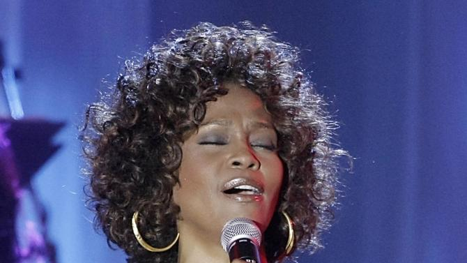"FILE - In this Feb. 7, 2009 file photo, singer Whitney Houston performs at the Clive Davis pre-Grammy party in Beverly Hills, Calif.  A CD/DVD featuring Whitney Houston's first public performance and her last one in 2012 will be released on Nov. 11, 2014. ""Whitney Houston Live: Her Greatest Performances"" is the late singer's first live album. Her mentor, Clive Davis, said the album will showcase the best-selling singer's legacy. (AP Photo/Dan Steinberg, file)"