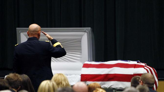 """FILE - In this Saturday, March 3, 2012 file photo, Maj. Gen. David Quantock salutes Army Sgt. Timothy John Conrad, 22, who was killed in Afghanistan last week, at Conrad's funeral at Northside High School's auditorium in Roanoke, Va.. The 22-year-old Conrad was one of two U.S. military police officers killed Feb. 23 by an Afghan soldier amid anti-American sentiment over the burning of Qurans at a U.S. military base. The Afghan government is blaming the onslaught of attacks by Afghan police and soldiers against international forces on """"infiltration by foreign spy agencies."""" Presidential spokesman Aimal Faizi told reporters Wednesday, Aug. 22, 2012 that intelligence services, including those in neighboring countries, are playing a part in most insider attacks.(AP Photo/The Roanoke Times, Rebecca Barnett, File)"""