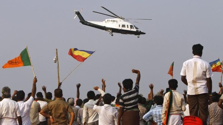 Supporters wave to a helicopter carrying Hindu nationalist Modi after a public meeting at Krishnagiri