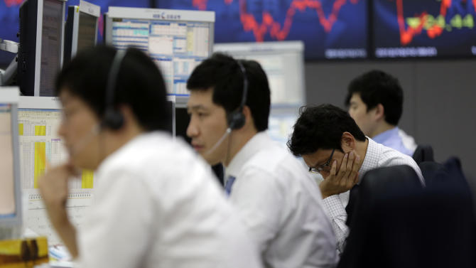 Currency traders work at the foreign exchange dealing room of the Korea Exchange Bank headquarters in Seoul, South Korea, Wednesday, Oct. 10, 2012. Worries about Europe's debt crisis, signs of weak global growth and expectations of lower U.S. corporate earnings sent most Asian stock markets down Wednesday. South Korea's Kospi dropped 1.4 percent at 1,955.84. (AP Photo/Lee Jin-man)