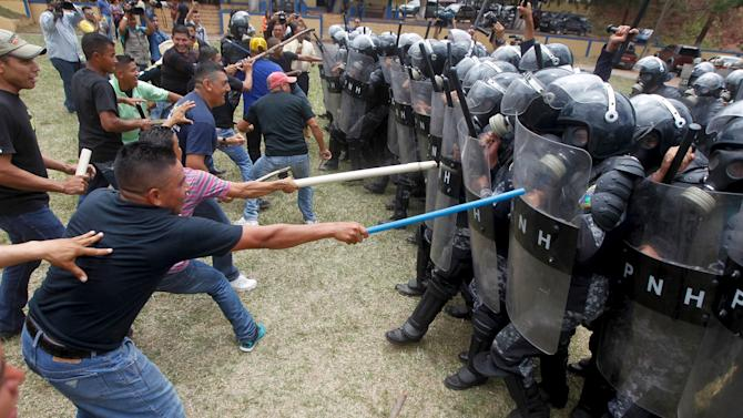 Mock rioters clash with members of the police unit for riot for law and order restoration, during a drill at a base in Tegucigalpa