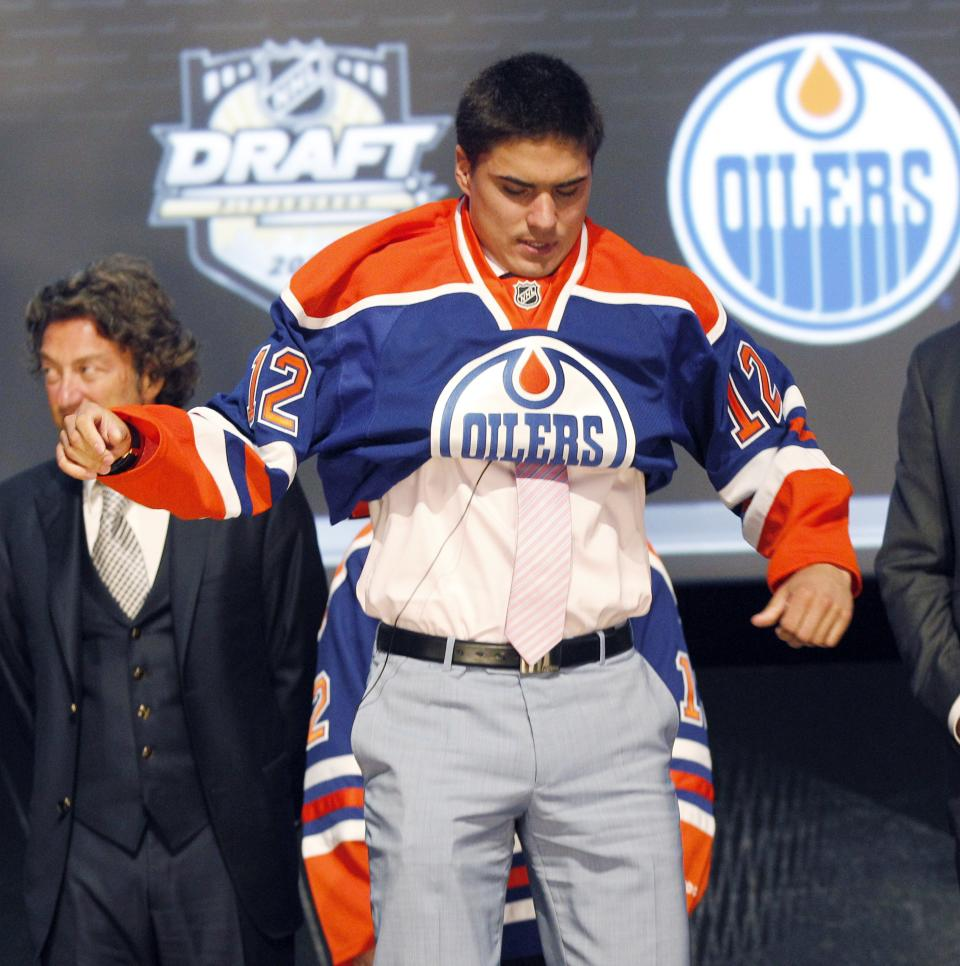 Nail Yakupov, a winger from Russia who was chosen first overall by the Edmonton Oilers in the first round of the NHL hockey draft, pulls on an Oilers jersey on Friday, June 22, 2012, in Pittsburgh. (AP Photo/Keith Srakocic)