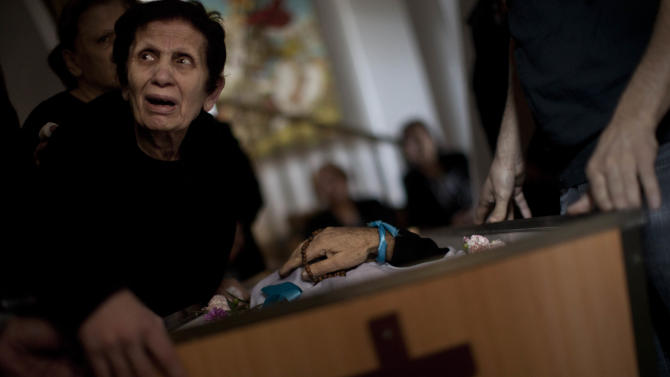 A Palestinian mourner cries during the funeral of Salem Paul Sweliem in Gaza City, Tuesday, Nov. 20, 2012. According to the family, the 52 years old  Greek Orthodox Christian carpenter was killed during an Israel Air Force strike on a high-rise building, in which  Ramez Harb, a senior figure in Islamic Jihad's military wing, was killed. Sweliem was in car when the strike took place and he died on his way to the hospital from shrapnel wounds. (AP Photo/Bernat Armangue)