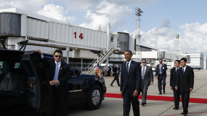 U.S. President Barack Obama, center, walks to his motorcade vehicle as he arrives on Air Force One at Don Mueang International Airport in Bangkok, Thailand, Sunday, Nov. 18, 2012. (AP Photo/Carolyn Kaster)