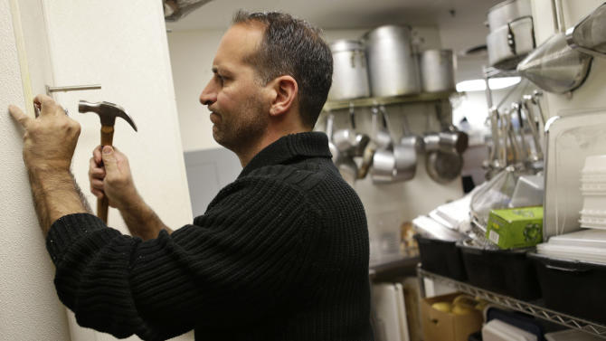 In this Monday, Oct. 8, 2012 photo, Anthony Cavallo, owner of the restaurant Vintage 50, mounts a potato cutter in his restaurant in Leesburg, Va. Cavallo, who does much of his own maintenance in his restaurant, says lingering questions about the economic future hurt business. He closed two restaurants in the last year. (AP Photo/Jacquelyn Martin)