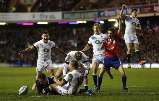 England's Burrell scores a try and is congratulated by team mates as Scotland's Greig Laidlaw fails to tackle during their Six Nations rugby union match at Murrayfield Stadium in Edinburgh