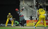 Afghanistan's batsman Mohammad Nabi (C) hits a six as Australian wicketkeeper Matthew Wade (L) looks on during an One Day International cricket match at the Sharjah cricket stadium. Former world champions Australia defeated a battling Afghanistan team by 66 runs in the first-ever limited overs international between the two sides