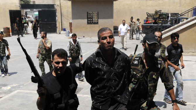 In this photograph made on  Friday, July 27, 2012, Syrian rebels arrest a man who they said was a government informant  in Aleppo, Syria. (AP Photo/Alberto Prieto)
