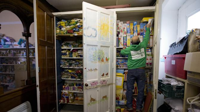 """In this photo taken Friday, April 5, 2013, a volunteer reaches up to put a box of cereal on a shelf at a food bank in St Luke's Church in the West Norwood area of London. It's possible that official figures on first quarter economic growth, to be released Thursday, could put the country back in recession. It would take the smallest statistical variation to put the figure in negative territory which would place the country in recession, another recession _ the third since the 2008 financial crisis _ and is already being referred to with foreboding in the media as a """"Triple Dip"""". (AP Photo/Matt Dunham)"""