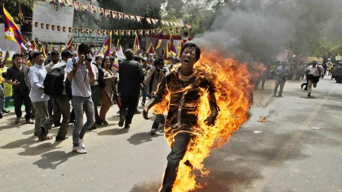 FILE - In this March 26, 2012 file photo, Tibetan exile Jamphel Yeshi screams as he runs engulfed in flames after setting himself on fire at a protest in New Delhi, India, against Chinese President Hu Jintao's visit to India. Yeshi died Wednesday, March 28, 2012.  (AP Photo/Manish Swarup, File)