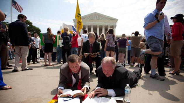 Demonstrators pray outside the Supreme Court.