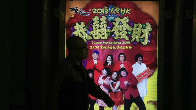 """In this Wednesday Feb. 13, 2013 photo, a man walks past the advertisement of a Hong Kong movie """" I Love Hong Kong 2013 """" in Hong Kong. Tens of millions of film fanatics are entering theaters around Asia during the long Lunar New Year holiday. This year's Hong Kong holiday crop includes """"Journey to the West: Conquering the Demons,"""" a prequel to the classic Chinese fable, and """"I Love Hong Kong 2013,"""" a super-light comedy with an all-star cast and a crowd-pleasing happy ending. Explaining her preference for watching locally-produced comedies, Hong Kong movie-goer Christine Lam said it reinforced the spirit of the season. (AP Photo/Vincent Yu)"""