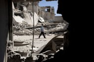A Syrian man walks past destroyed buildings in Al-Bab in the northern province of Aleppo