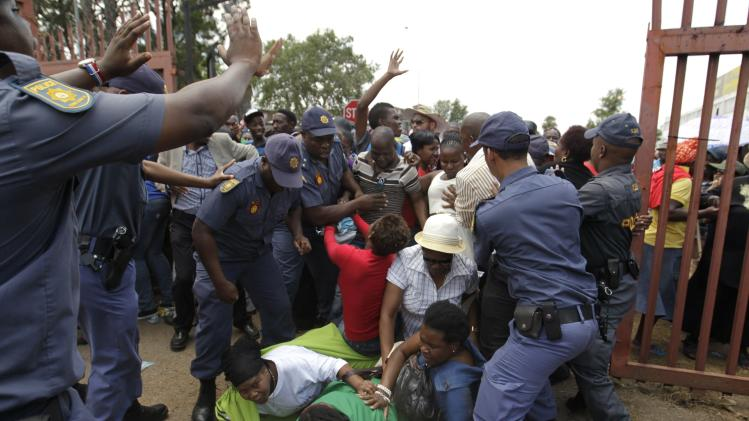 Mourners fall during a stampede as they run to queue before boarding buses to take them to the Union Buildings, where former South African President Mandela is lying in state, in Pretoria