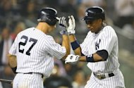 Curtis Granderson (R) of the New York Yankees celebrates his home run with Raul Ibanez during their game against the Boston Red Sox, on October 3, at Yankee Stadium in the Bronx borough of New York City. The Yankees claimed their 13th AL East crown in 17 years with a dominating 14-2 victory