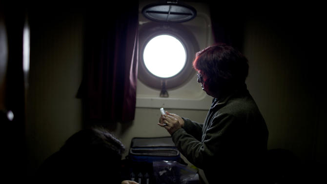 """In this Jan. 27, 2015 photo, Chilean biochemist Jenny Blamey looks at samples in her room aboard the Aquiles navy ship, near Antarctica's Almirantazgo Bay off Livingston Island, part of the South Shetland Island archipelago. """"You don't have to be a rocket scientist to look around and see how extreme this environment is,"""" said Blamey, the research director of the Biosciences Foundation in Chile who is studying the genetic material of microorganisms, essentially microbes that can't be seen. (AP Photo/Natacha Pisarenko)"""