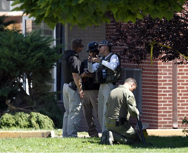 Federal agents outside the apartment of James Holmes in Aurora, Colo., Saturday, July 21, 2012.  Federal authorities detonated one small explosive and disarmed another inside Holmes' apartment, but se