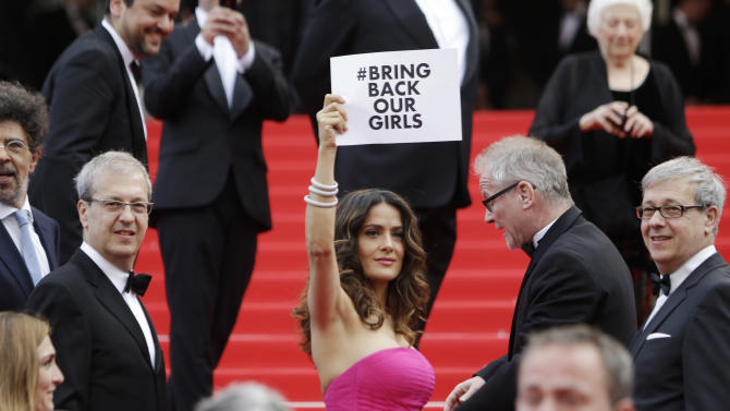 """Actress Salma Hayek holds up a sign reading """"bring back our girls"""", part of a campaign calling for the release of nearly 300 abducted Nigerian schoolgirls being held by Nigerian Islamic extremist group Boko Haram, as she arrives for the screening of Saint-Laurent at the 67th international film festival, Cannes, southern France, Saturday, May 17, 2014. (AP Photo/Thibault Camus)"""
