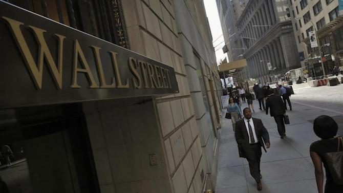 Morning commuters walk on Wall Street in New York's financial district