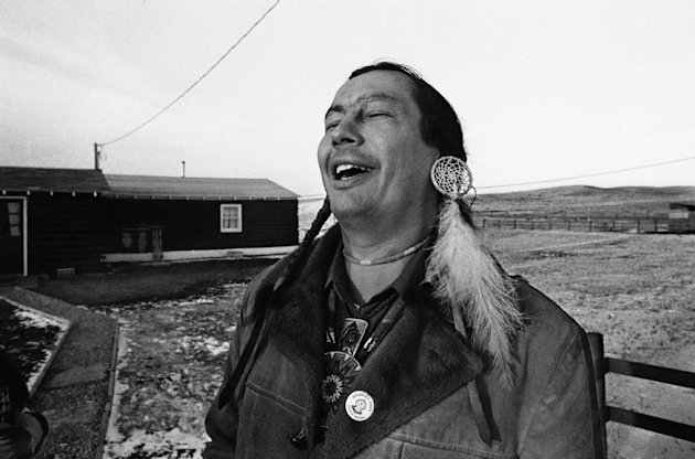 FILE - In a Feb. 4, 1974 file photo, American Indian Movement (AIM) leader Russell Means, who is challenging incumbent Oglala Sioux Tribal President Richard Wilson in Thursday&#39;s election on the Pine Ridge Indian Reservation, laughs at news report which quoted Wilson as saying he will give AIM 10 days to get off the reservation after he is reelected &quot;or else&quot;, in Pine Ridge, S.D. Means, a former American Indian Movement activist who helped lead the 1973 uprising at Wounded Knee, reveled in stirring up attention and appeared in several Hollywood films, died early Monday, Oct. 22, 2012 at his ranch in in Porcupine, S.D., Oglala Sioux Tribe spokeswoman Donna Solomon said. He was 72. (AP Photo/Jim Mone, File)