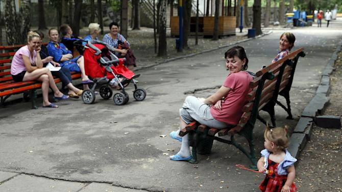 Adults look at a girl as they sit on benches in the compound of a health and rest centre which serves as a temporary accommodation for refugees from eastern regions of the country in the town of Korostyshiv