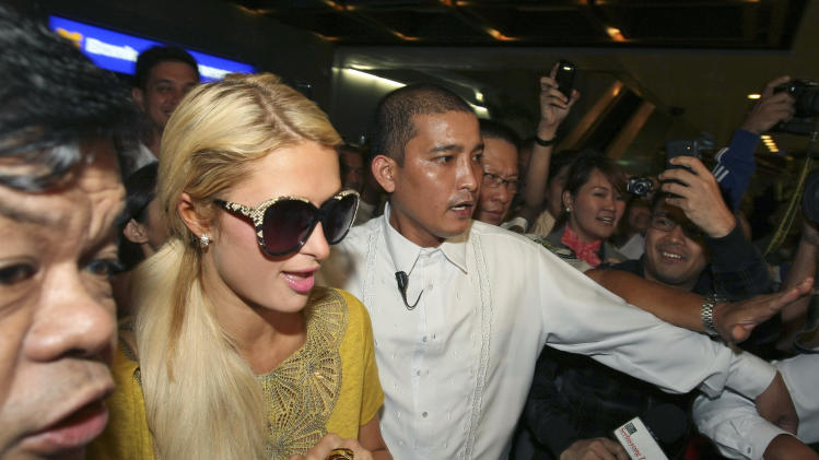 American heiress and media personality Paris Hilton is escorted to her limousine shortly upon arrival at the Ninoy Aquino International Airport in Manila, Philippines late Sunday Aug.14, 2011. Ms. Hilton is in Manila to meet with her friend, Filipino boxing champion Manny Pacquiao and his wife Jinkee as well as inaugurate her Paris Hilton boutique and promote a beach resort. (AP Photo/Bullit Marquez)
