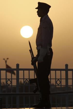 A Pakistan Air Force cadet is silhouetted while he stands guard during a change of guard ceremony to mark the 135th anniversary of the birth of Mohammed Ali Jinnah, founder of Pakistan, at the Jinnah mausoleum in Karachi, Pakistan, Sunday, Dec. 25, 2011. (AP Photo/Fareed Khan)