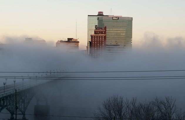 A fog rises off the Tennessee River that partially obscures a view of downtown Knoxville. (AP Photo/The Knoxville News Sentinel, J. Miles Cary)