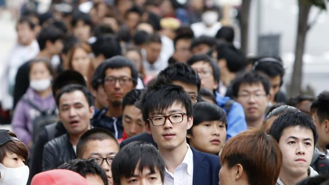 People wait for the release of Apple's new iPhone 6 and 6 Plus in Tokyo