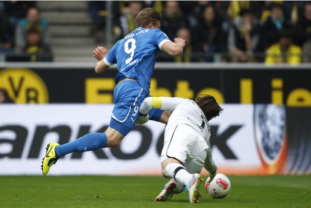 Borussia Dortmund's Weidenfeller tackles Hoffenheim's Schipplock during the German first division Bundesliga soccer match against Hoffenheim in Dortmund
