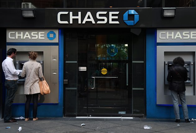 In this May 6, 2012, photo, people use Chase ATM machines at a branch in New York. Americans stepped up their borrowing in May, helped by the largest one-month gain in credit card debt in more than four years. But overall credit card use is still well below where it was just before the Great Recession began. (AP Photo/CX Matiash)