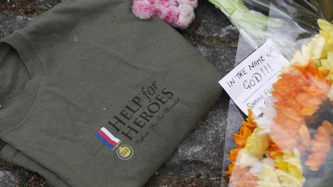 A 'Help for Heroes' T-shirt and floral tributes in memory of the victim lay on the pavement outside the Royal Artillery Barracks near the scene of a terror attack in Woolwich, southeast London, Thursday, May 23, 2013. The British government's emergency committee met Thursday after two attackers killed a man in a daylight attack in London that raised fears terrorism had returned to the capital. (AP Photo/Sang Tan)