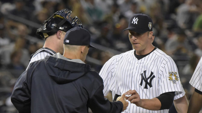 New York Yankees pitcher Chris Capuano hands the ball to manager Joe Girardi, left, as Capuano comes out of the baseball game during the fifth inning against the Texas Rangers  Sunday, May 24, 2015, at Yankee Stadium in New York. (AP Photo/Bill Kostroun)