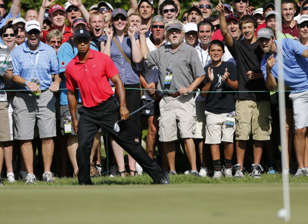 Tiger Woods, foreground left, reacts after his chip onto the green failed to drop into the hole on the seventh green during the final round of the Deutsche Bank Championship PGA golf tournament at TPC Boston in Norton, Mass., Monday, Sept. 3, 2012. (AP Photo/Michael Dwyer)