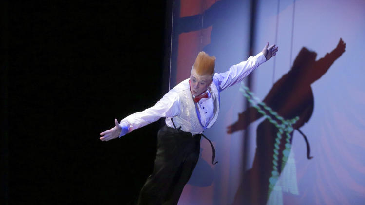 """This March 23, 2013 photo shows Bello Nock, performing a stunt with the assistance of a young audience member, during his """"Bello Mania"""" show at the New Victory Theater in New York.  Nock, a seventh-generation circus performer, is never offstage during the 90-minute performance, which combines slapstick clowning with death-defying aerial stunts. He performs through March 31 at the New Victory before moving on to the Canadian side of Niagara Falls and then a 10-week stint at the Beau Rivage Casino in Biloxi, Miss.  (AP Photo/Richard Drew)"""