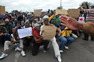 Demonstrators hold placards during a march by protesting miners in Rustenburg after a security crackdown in the restive platinum belt where officers shot dead 34 strikers exactly a month ago. South Africa's President Jacob Zuma denied Sunday his government had embraced apartheid measures in a crackdown on protesting mineworkers