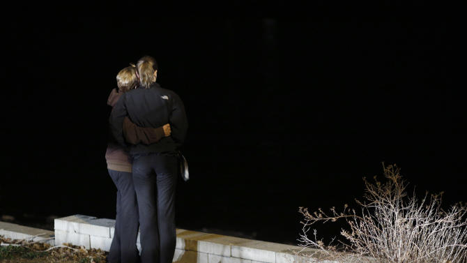 Two people embrace after a vigil held at Meyers lake Wednesday, Dec. 5, 2012, in Evansdale, Iowa.  Hunters discovered two bodies Wednesday believed to be the young Iowa cousins who vanished five months ago while riding their bikes, authorities said. (AP Photo/Waterloo Courier, Matthew Putney)
