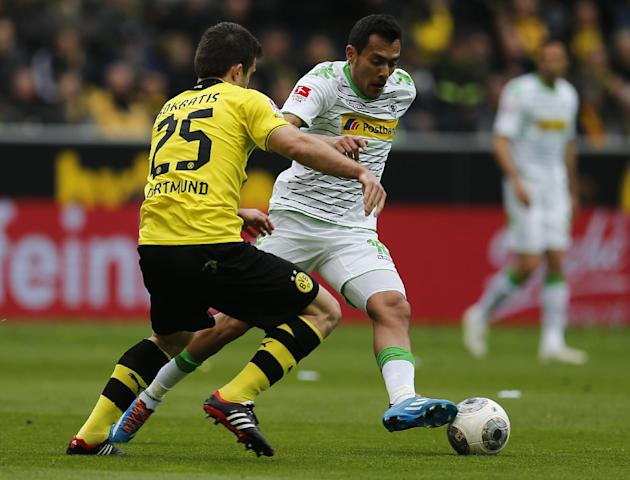 Dortmund's Sokratis of Greece, left, and Moenchengladbach's Raffael of Brazil challenge for the ball during the German first division Bundesliga soccer match between BvB Borussia Dortmund and