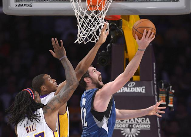 Minnesota Timberwolves forward Kevin Love, right, puts up a shot as Los Angeles Lakers center Jordan Hill, left, and guard Wesley Johnson defend during the first half of an NBA basketball game, Sunday