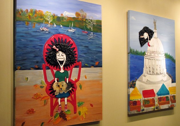 Paintings imagining comedian Gilda Radner in recognizable locations in Madison hang on the wall inside the cancer support group Gilda&#39;s Club Madison on Wednesday, Nov. 27, 2012, in Middleton, Wis. The Madison-area chapter of the national group is the latest to change its name to the Cancer Support Community, a move its director said was necessary because young people don&#39;t know who Radner was. (AP Photo/Scott Bauer)