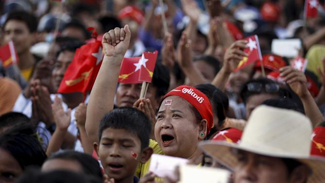 Supporters stand during Myanmar pro-democracy leader Aung San Suu Kyi's speech during her visit to Mawhlamyaing township in Mon state