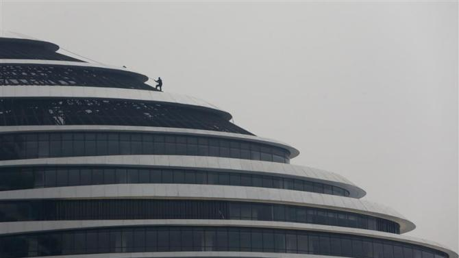 A labourer works on the roof of a new building in Beijing