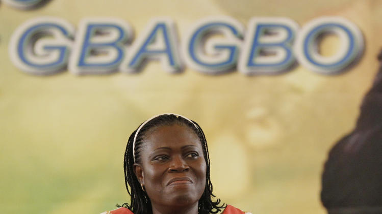 FILE - This is a Saturday, Jan. 15, 2011 file photo of Simone Gbagbo, wife of Laurent Gbagbo, reacts during a pro-Gbagbo rally at the Palace of Culture in the Treichville neighborhood of Abidjan, Ivory Coast. The International Criminal Court said it has indicted Simone Gbagbo, the wife of former Ivory Coast president Laurent Gbagbo, on charges including murder, rape and persecution. The court announced Thursday Nov. 22, 2012 it had unsealed an arrest warrant issued Feb. 29 for the first woman indicted by the world's first permanent war crimes court. (AP Photo/Rebecca Blackwell, File)