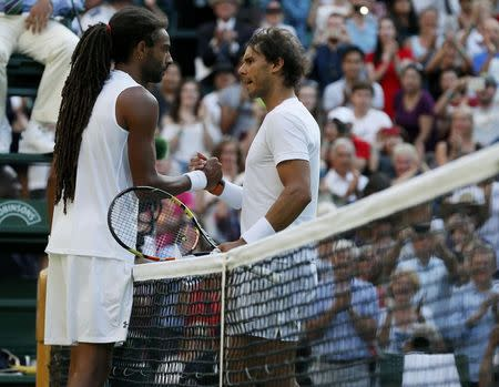 Dustin Brown of Germany shakes hands with Rafael Nadal of Spain after winning their match at the Wimbledon Tennis Championships in London