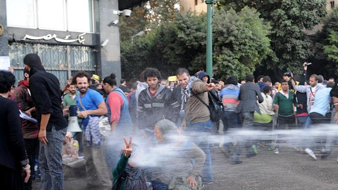 Egyptian police fire water cannons to disperse a protest by secular anti-government activists in Cairo, Tuesday, Nov. 26, 2013, the security forces' first implementation of a controversial new law forbidding protests held without a permit from authorities. (AP Photo/Mohammed Asad)
