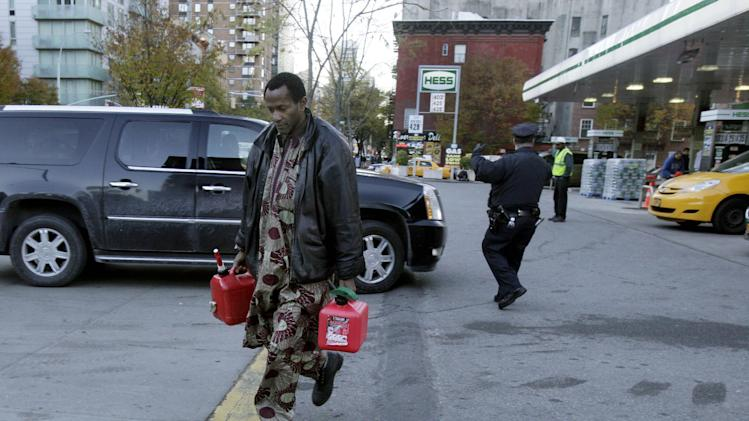 A man carries two filled gas cans at a gasoline station, in New York, Friday, Nov. 9, 2012. A new gasoline rationing plan that lets motorists fill up every other day went into effect in New York on Friday morning. Police were at gas stations to enforce the new system in New York City and on Long Island.  (AP Photo/Richard Drew)