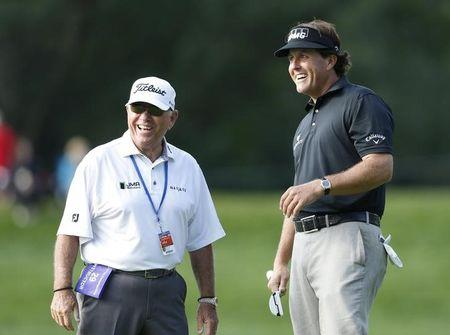 Mickelson of the U.S. walks to the third green with his swing coach Harmon during a practice round for the 2013 PGA Championship golf tournament at Oak Hill Country Club in Rochester