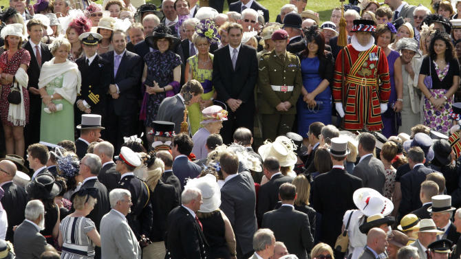 Britain's Queen Elizabeth II, center, walks past guests during the annual summer garden party held at Buckingham Palace in London, Wednesday, June 29, 2011. At a typical Buckingham Palace garden party, around 27,000 cups of tea, 20,000 sandwiches and 20,000 slices of cake are consumed, with Some 400 waiting staff involved in the serving. (AP Photo/Matt Dunham, Pool)