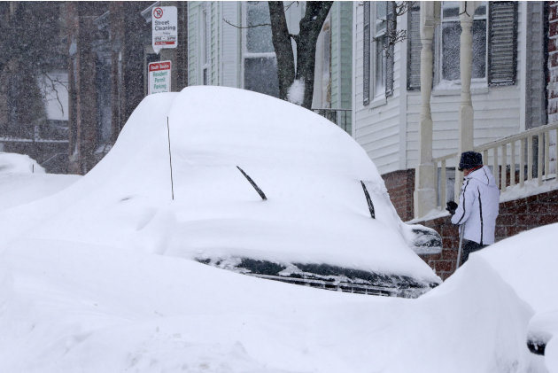 A woman shovels out a car on Third street in the South Boston neighborhood of Boston on Saturday, Feb. 9, 2013. A behemoth storm packing hurricane-force wind gusts and blizzard conditions swept throug