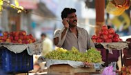 An Indian fruit vendor speaks on his mobile phone at a market in Allahabad on February 28, 2013. Health-related applications for smartphones and tablets are a booming business, but in Africa and Asia &quot;mobile health&quot; could actually be a lifesaver for millions, industry leaders and aid organisations say